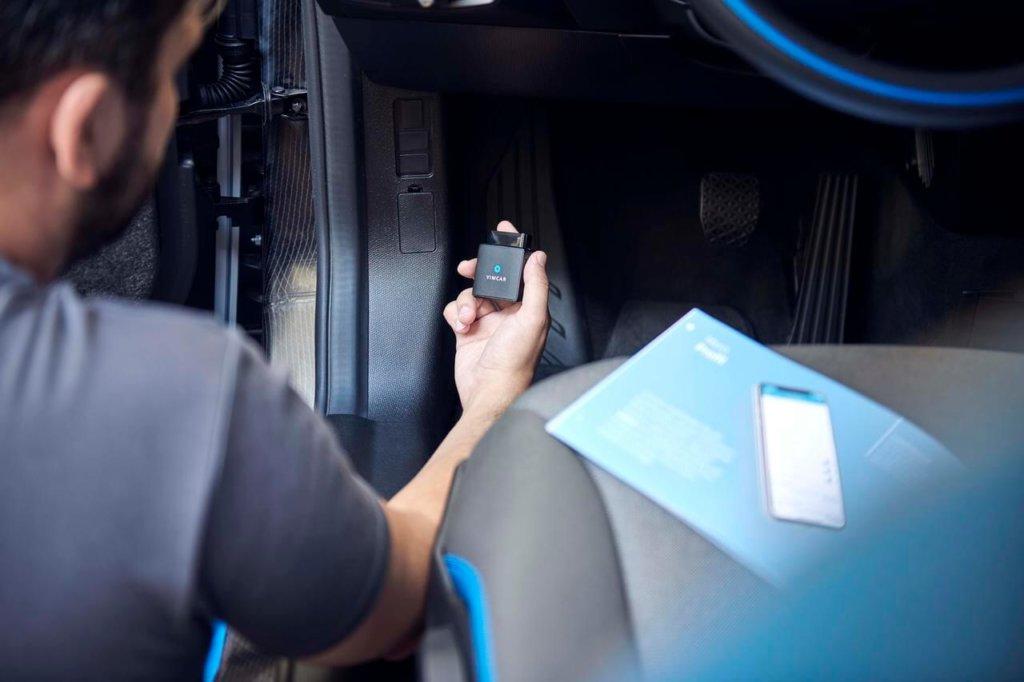 obd2-stecker von vimcar im fußraum vom auto