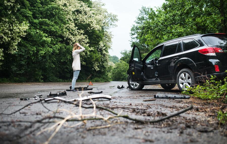 frau steht vor auto mit schaden