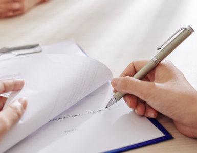person unterschreibt formulare