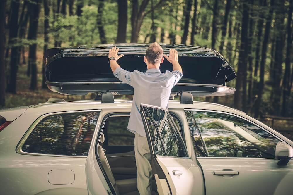 mann befestigt dachbox auf auto