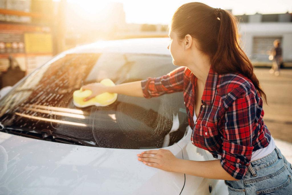 frau reinigt autoscheiben von aussen