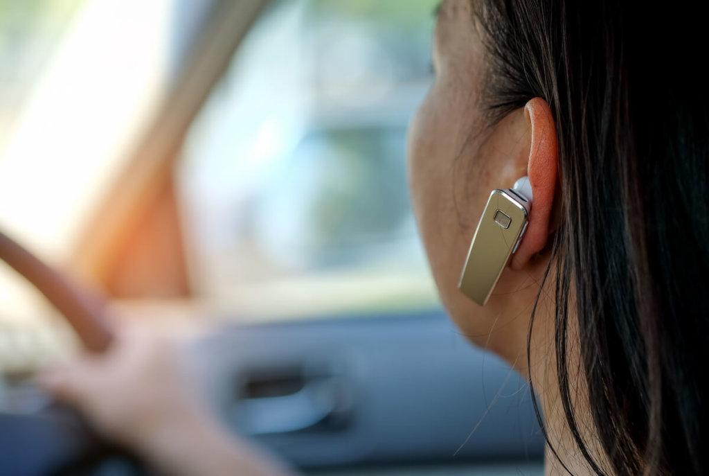 frau im auto mit einem headset für eine freisprechanlage