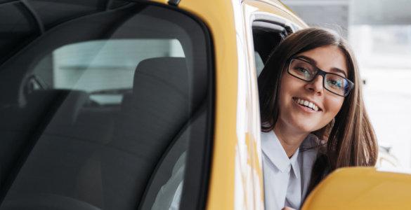 lachende junge Frau in Auto